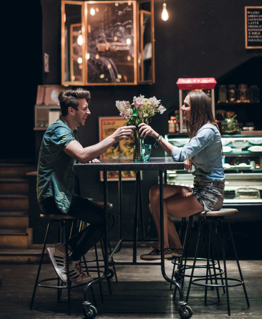 Two young urban diners sitting at modern eatery table in open concept restaurant