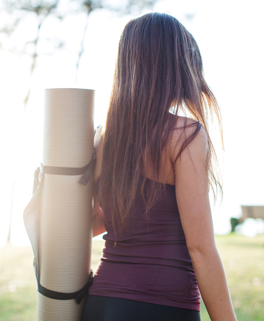 Young urban woman carrying a yoga mat in an outdoor green space