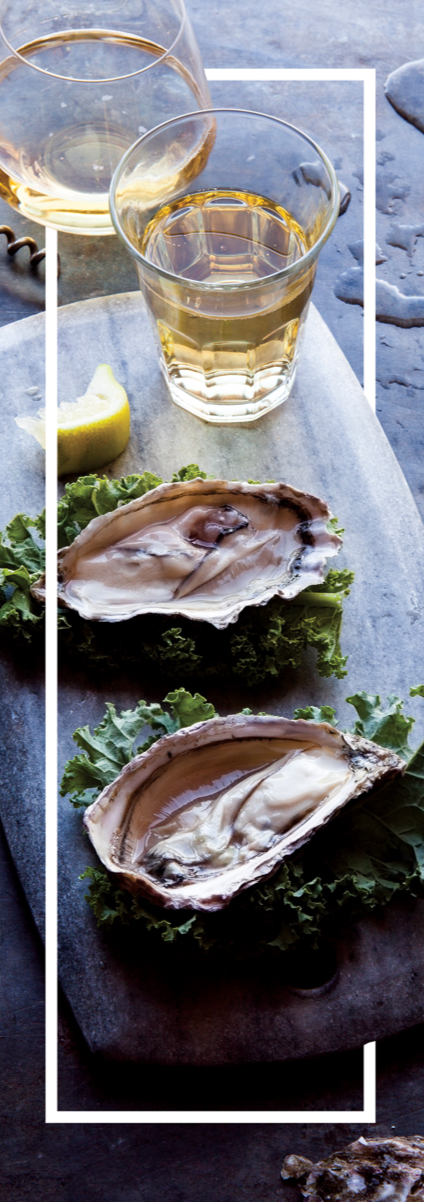 Glasses of wine on a board with oysters