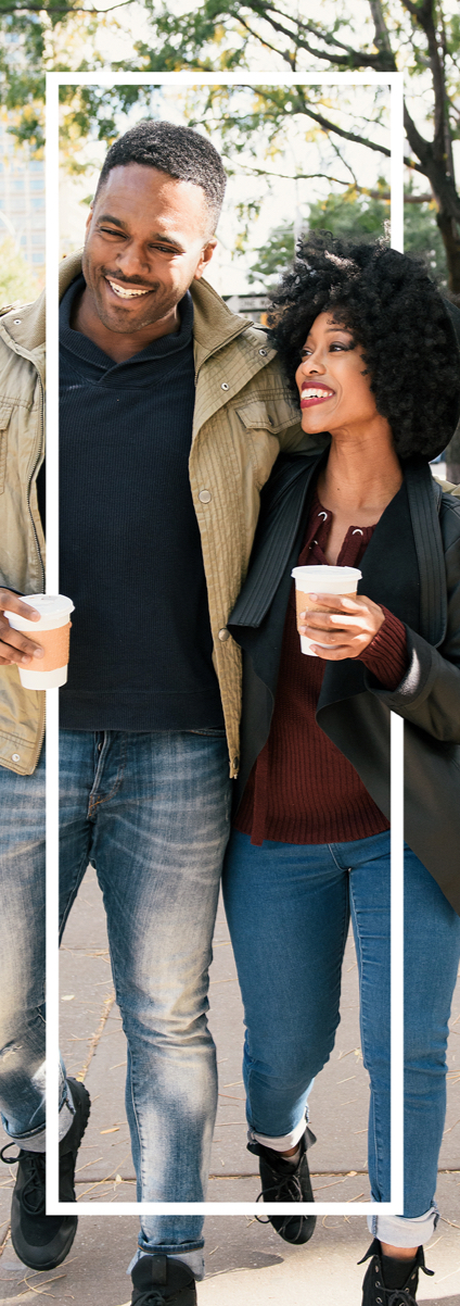 Couple walking and laughing holding a cup of coffee