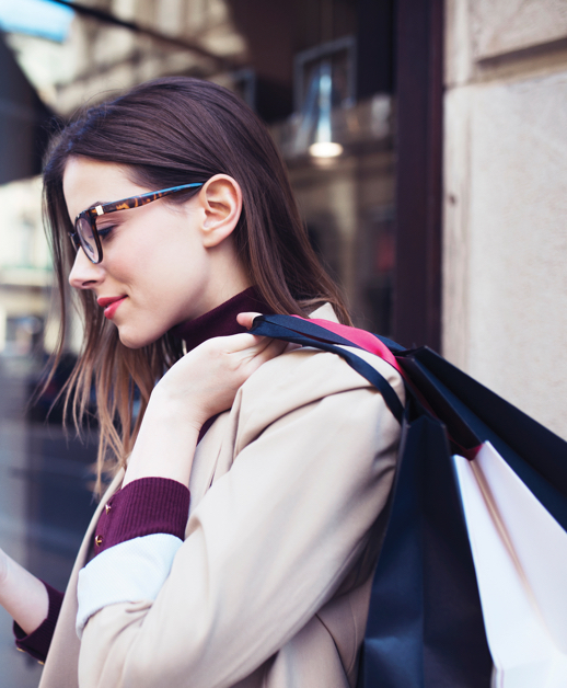 Young stylish urban woman carrying shopping bags and checking phone